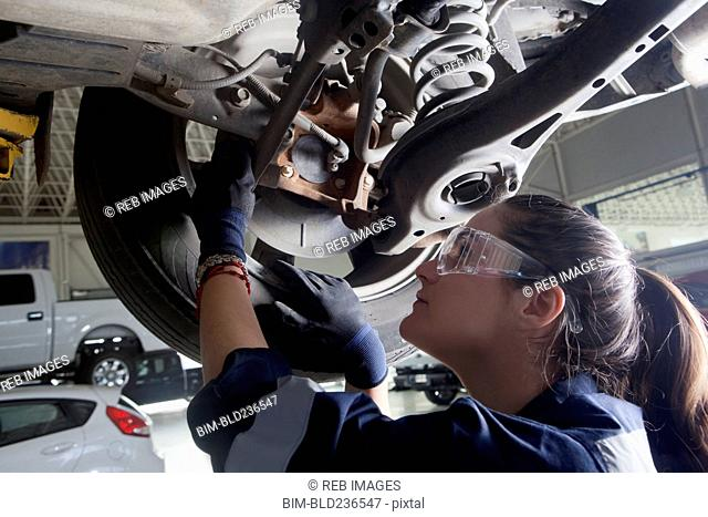 Hispanic mechanic repairing car