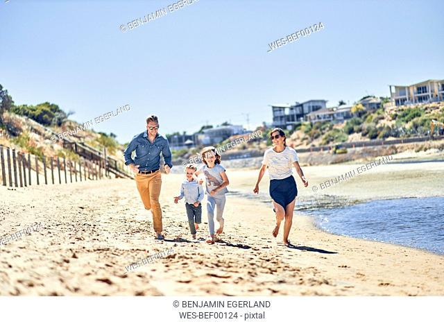 Australia, Adelaide, Onkaparinga River, happy family running on the beach together