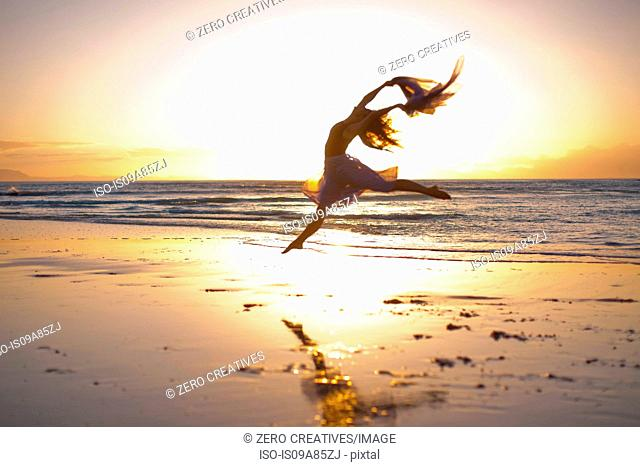 Young woman dancing on sunlit beach