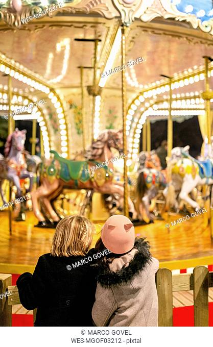 Two girls looking at a Christmas carousel