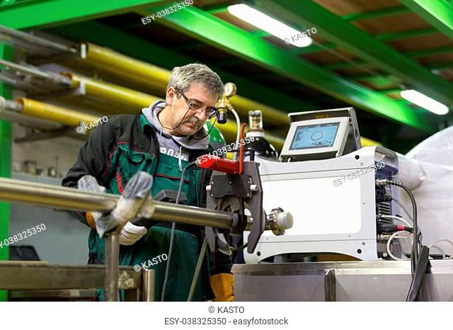 Industrial operator setting computer controlled process of orbital welding machine in inox pipes manufacturing workshop