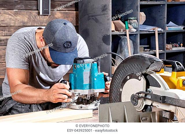 A young man with a gray cap carpenter builder in work clothes handles a wooden plank with a milling machine in the workshop, around a lot of equipment