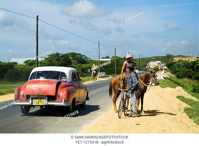 Classic American car passing by a cowboy and a cyclist talking on a countryside road, Cuba