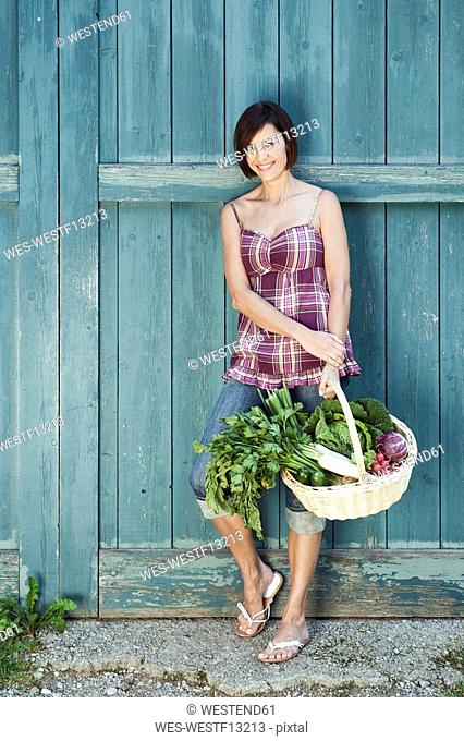 Germany, Bavaria, Woman in front of barn door holding basket with fresh vegetables, smiling, portrait