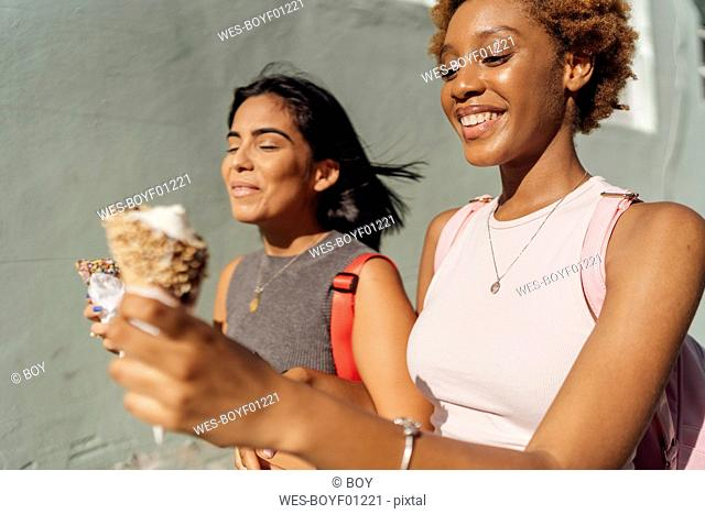 Two happy female friends with ice cream cones outdoors
