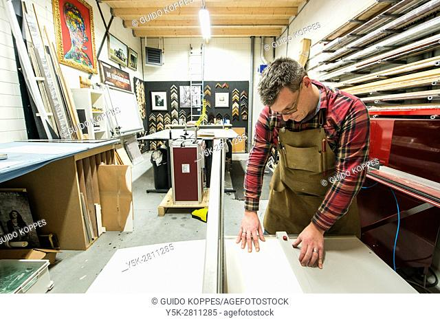 Goirle, Netherlands. Mid adult male craftsman and picture framemaker, cutting up paper and karton for some new passepartouts