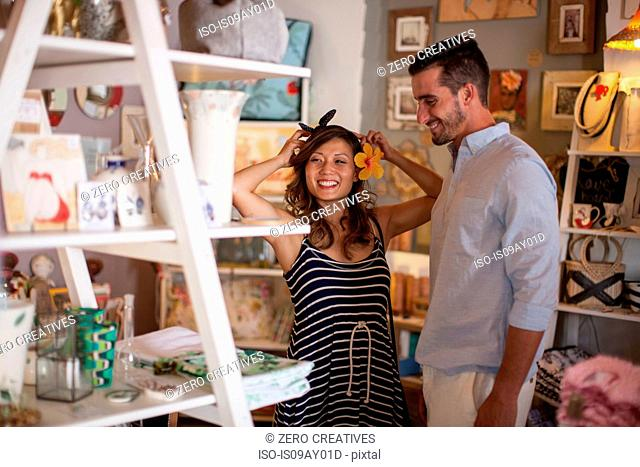 Shopping couple trying on flower headdress in gift shop