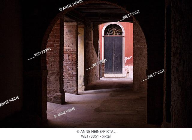 Dark arkade with illuminated warm coloured wall with door at the end. In Venice, Italy
