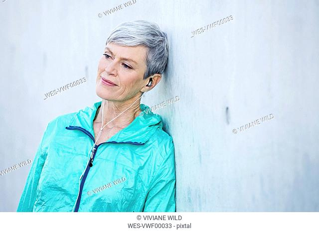 Smiling sporty mature woman with earbuds leaning against concrete wall