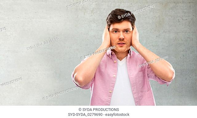 man closing ears by hands over gray concrete wall