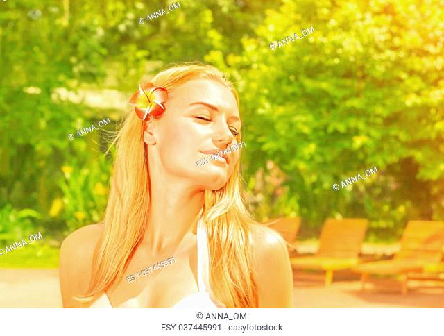 Closeup portrait of beautiful woman with closed eyes and red frangipani flower in hair, enjoying warm sunny day in fresh green garden, summer holiday concept