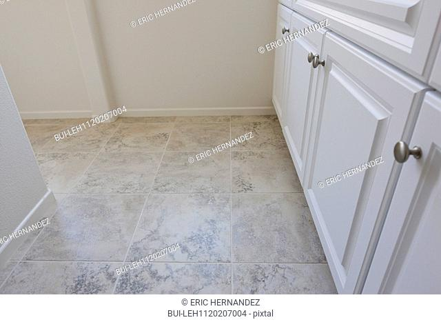 High angle view of cropped white cabinets and tiled floor at home