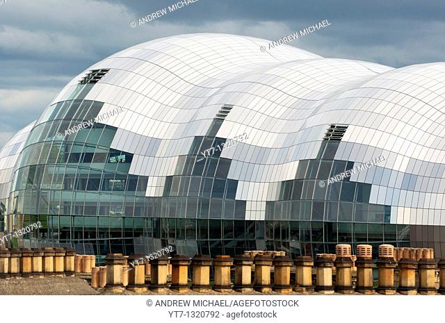 The Sage building in Newcastle up Tyne seen above old chimney tops  England