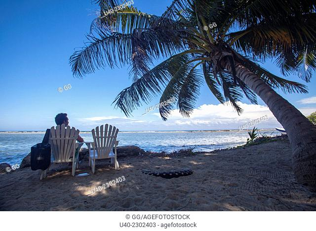 Man sitting alone on the beach, Tobacco Caye, Belize