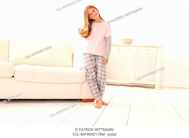 Girl in pajamas leaning on couch