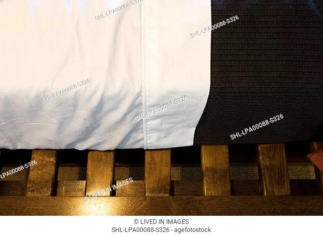 Detail sheets and blanket on bed on wood slated bed frame