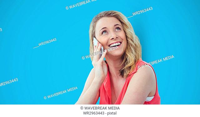 Happy female hipster using smart phone against blue background