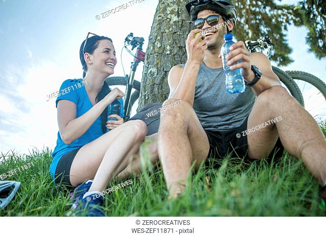 Young couple mountain biking in nature, taking a break under tree