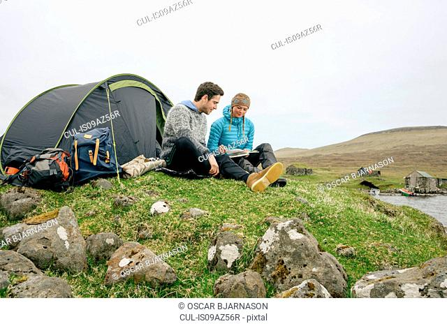 Campers relaxing and reading book beside tent, Vagar, Faroe Islands
