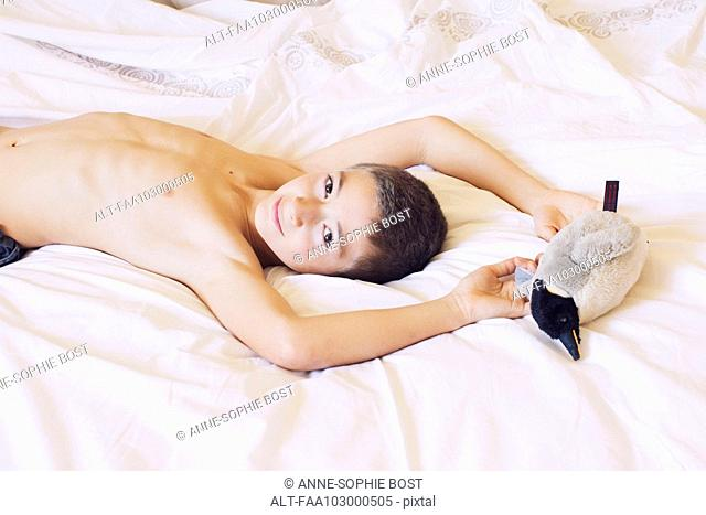 Boy lying on bed with stuffed penguin, portrait
