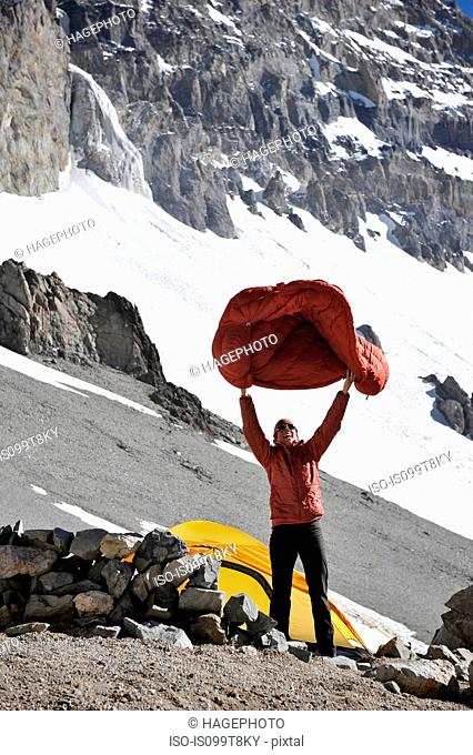 Woman shakes her sleeping bag at Camp One on Aconcagua in the Andes Mountains, Mendoza Province, Argentina