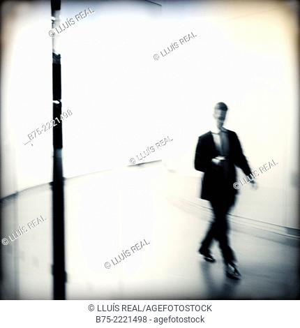 Solo Executive, unrecognizable walking between buildings in an urban space in the City of London, England, UK