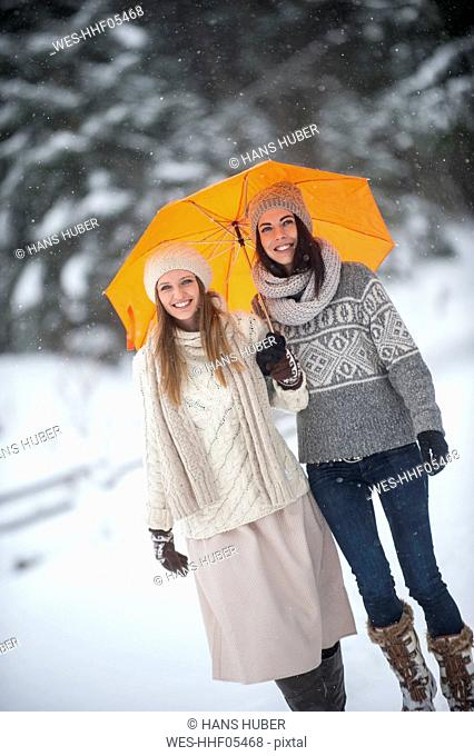 Portrait of two friends with yellow umbrella in winter