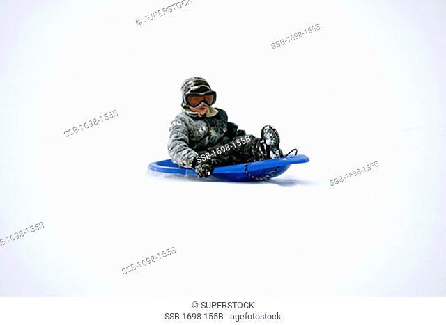 Boy sitting on a sled and sledding