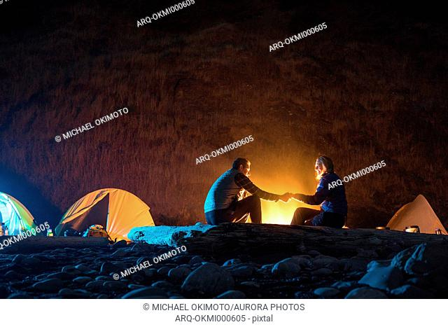 Couple holding hands by campfire while camping at night at Lost Coast Trail, California, USA