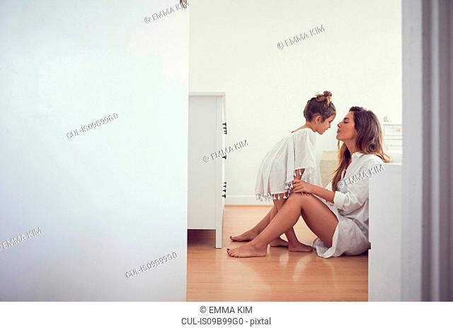 Young girl standing beside mother in bedroom, face to face