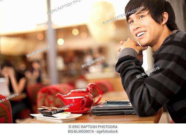 Smiling mixed race man at cafe