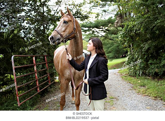 Equestrian woman walking horse on dirt path