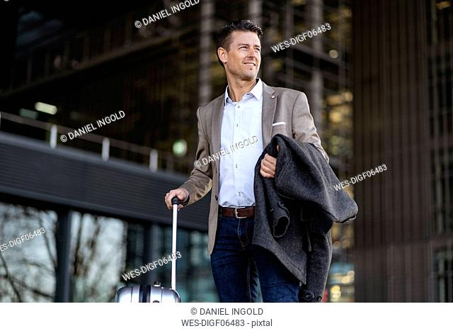 Businessman with suitcase standing outdoors