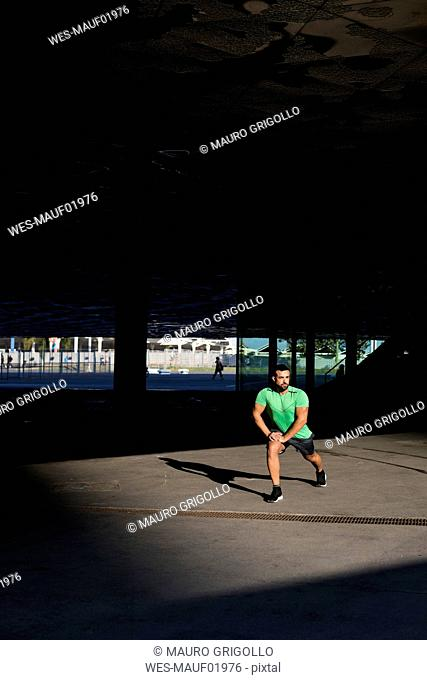 Sportive man during workout, stretching