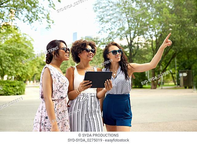 women with tablet pc on street in summer