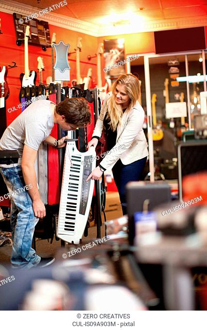 Young couple looking at keytar in music store