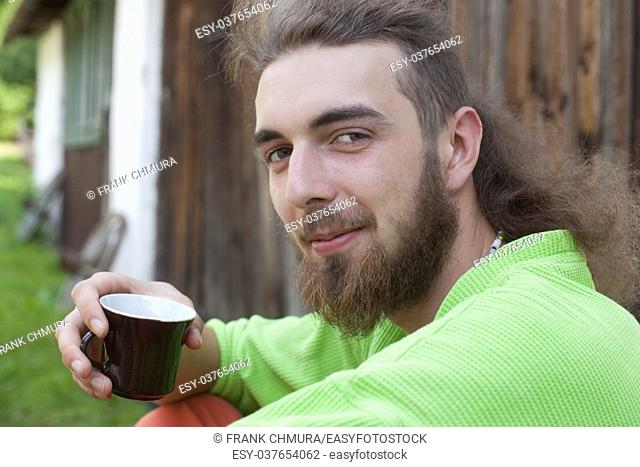 Portrait of a Teenage Boy with Long Hair and Beard Outdoors