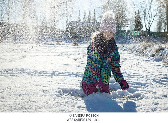 Girl throwing snow in the air
