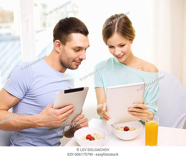 food, home, couple and technology concept - smiling couple with tablet pc reading news and having breakfast at home