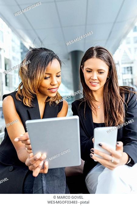 Two businesswomen working with smartphone and tablet in the city