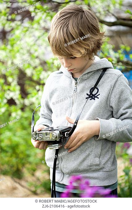 Boy with a old camera playing outdoors