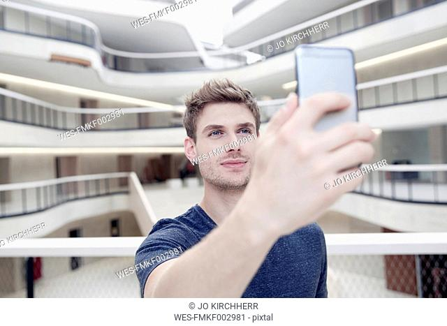 Young man taking a selfie in modern office building