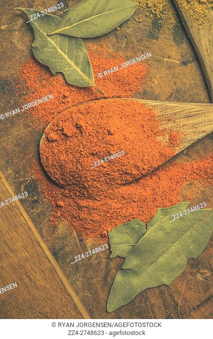 Directly above shot of chili powder on wooden spoon amidst bay leaves on table. Curry house in detail