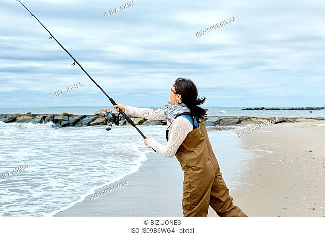 Young woman in waders casting sea fishing rod from beach