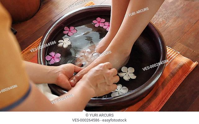 Cropped footage of a woman,s feet being washed gently by a professional masseuse