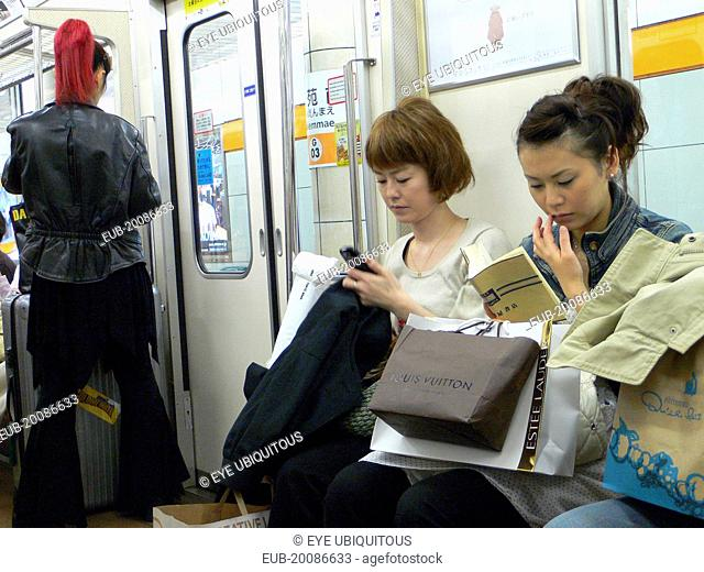 Ginza - three women on a subway train, right side young woman, shopping bags including Louis Vuitton, woman in the middle using cell phone text message