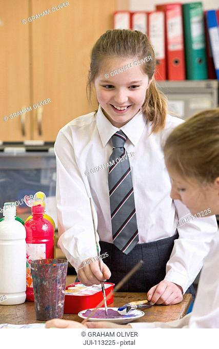 Smiling middle school student painting in art class