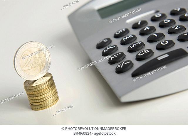 Stacked Euro coins next to a calculator