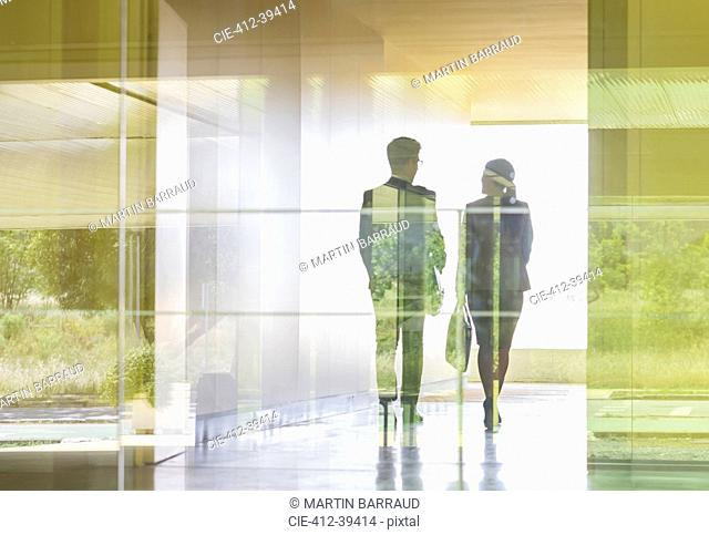 Silhouette business people walking in modern office corridor