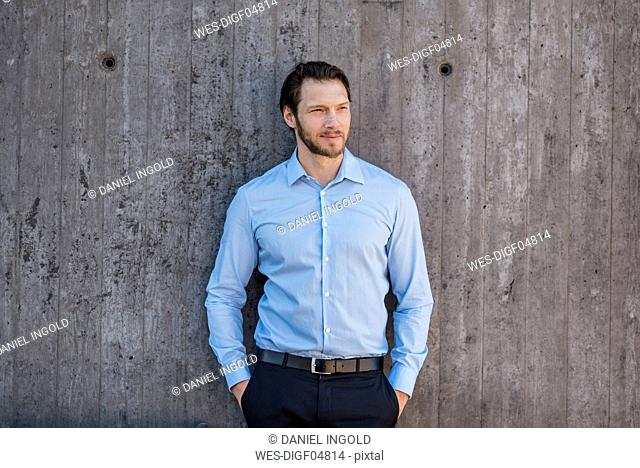Portrait of businessman standing at concrete wall